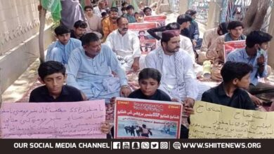 Shia Muslims sit in protest